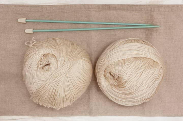 wo Balls of Cream Colored Cashmere Wool with straight knitting needles.