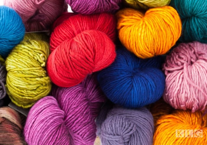 Image is colorful skeins of yarn in red, yellow, pink, green, purple.