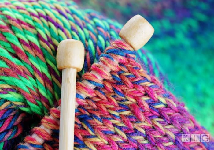 Colorful yarn knitted on wooden needles