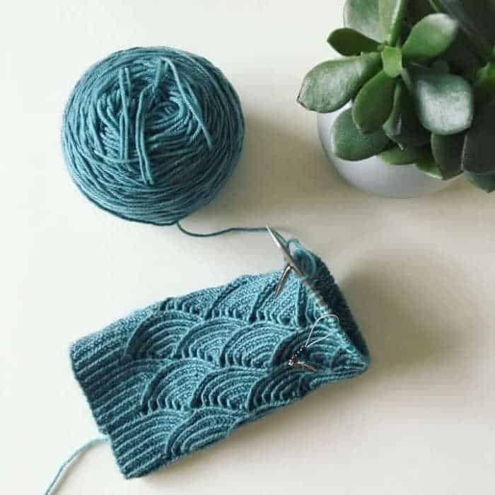 Socks on knitting needles in scallop pattern in teal blue yarn