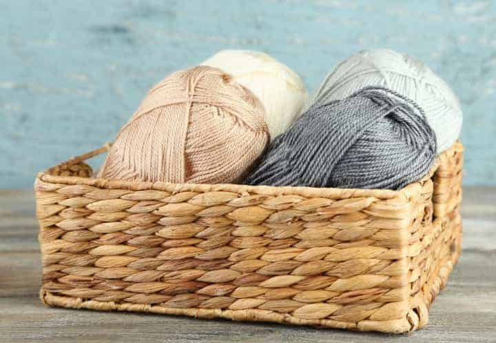 Organic Yarn stored in a raffia box of different greys and creams. Organic Yarn is not chemically treated.