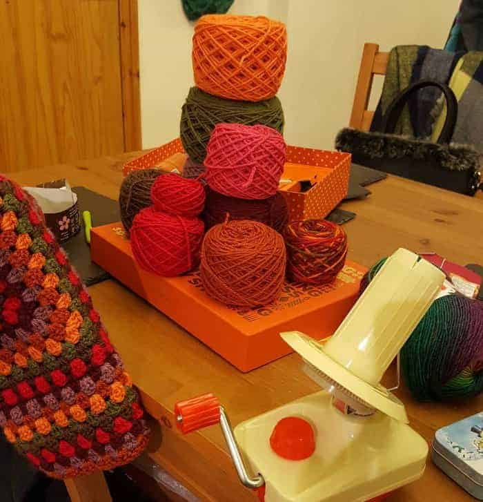 Yarn Winder and yarn cakes of different colors on a table