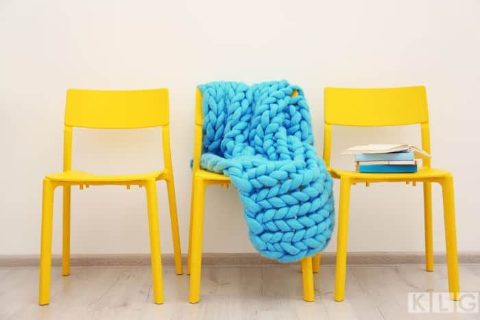 Blue color arm knitted blanket on yellow chairs