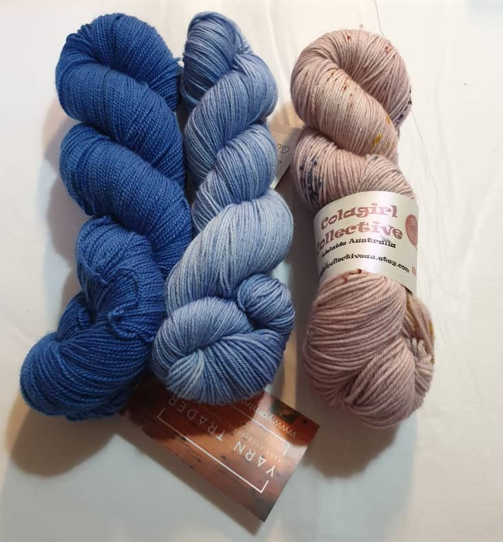 Yarn Trader Studio Skinny Sock Yarn from left to right Electric City (electric blue color), Caladan Waters (sky blue color), Speckled Pink Colagirl Collective Yarn