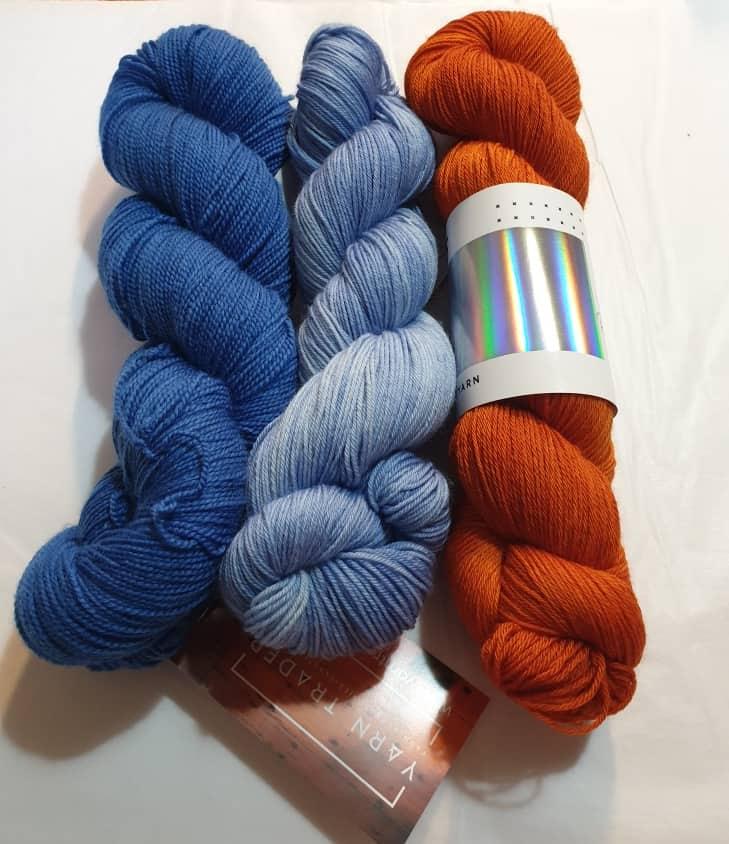 Yarn Trader Studio Skinny Sock Yarn from left to right Electric City (electric blue color), Caladan Waters (sky blue color), Hedgehog Fibers Burnt Orange yarn.