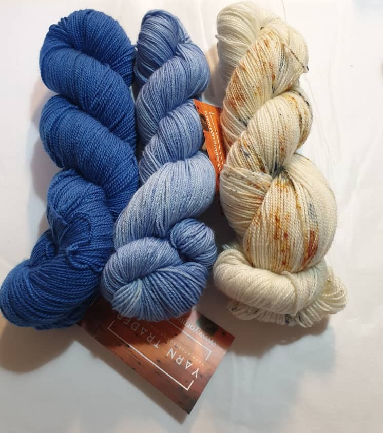 Yarn Trader Studio Skinny Sock Yarn from left to right Electric City (electric blue color), Caladan Waters (sky blue color), Speckled orange and blue with predominant cream color yarn