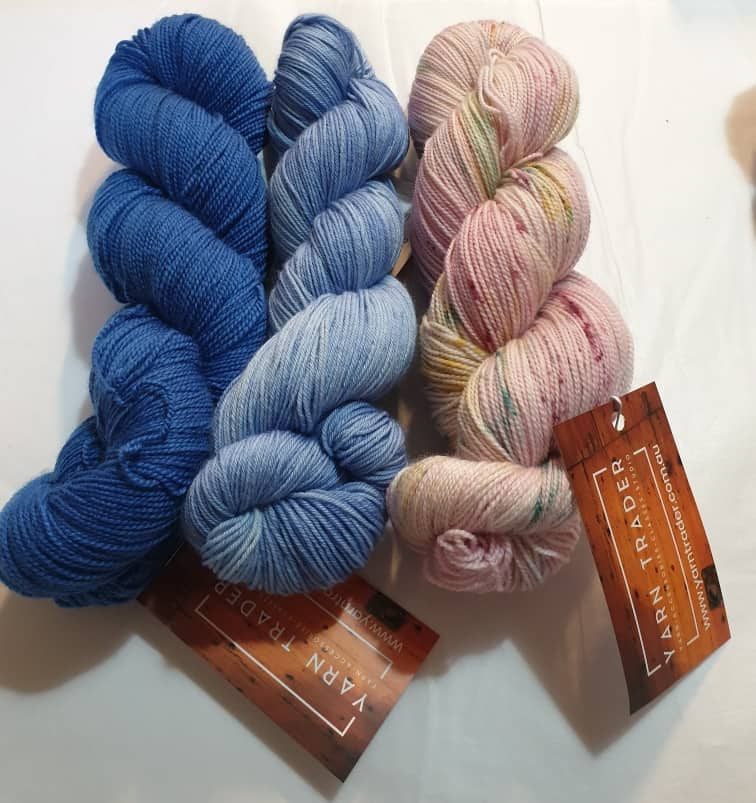 Yarn Trader Studio Skinny Sock Yarn from left to right Electric City (electric blue color), Caladan Waters (sky blue color),Speckled Pink yarn
