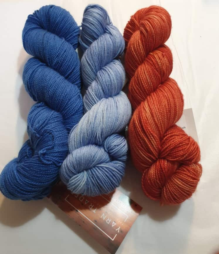 Yarn Trader Studio Skinny Sock Yarn from left to right Electric City (electric blue color), Caladan Waters (sky blue color), Coral (burnt orange color)