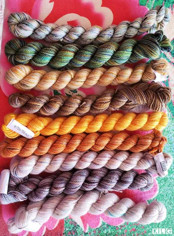 9 mini skeins of Koigu hand painted KPPM 100% merino yarns in  greens, browns, oranges, yellows and whites.