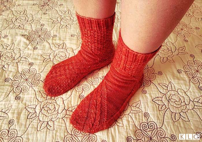 Top view of the two Smaug socks showing the gorgeous cable stitches and dragon scale stitch pattern with ribbed cuff in coral colored yarn