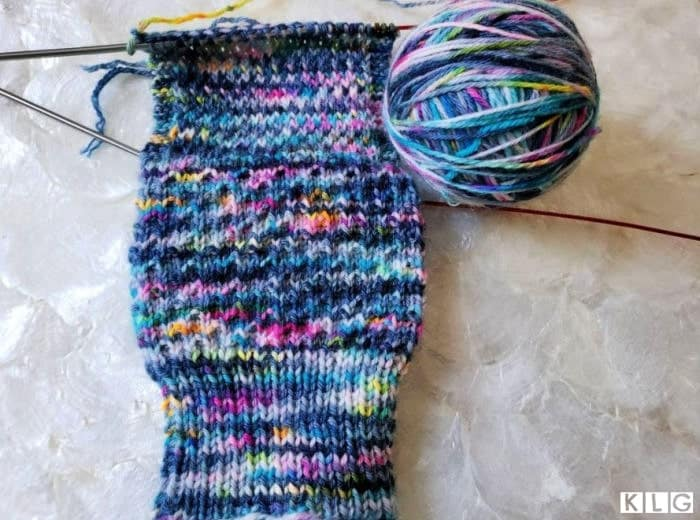 One sock at a time now showing the cuff, leg and the heel flap completed.