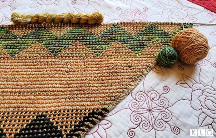 My Kentia wrap  showing the Koigu green multi colored yarn, pale caramel brown yarn and a mini skein of yarn in yellows and greens.