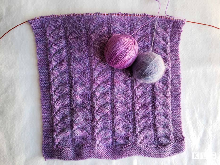 Overhead view of my Chasing Light Shawl with the two balls of Rose Hip Island yarns