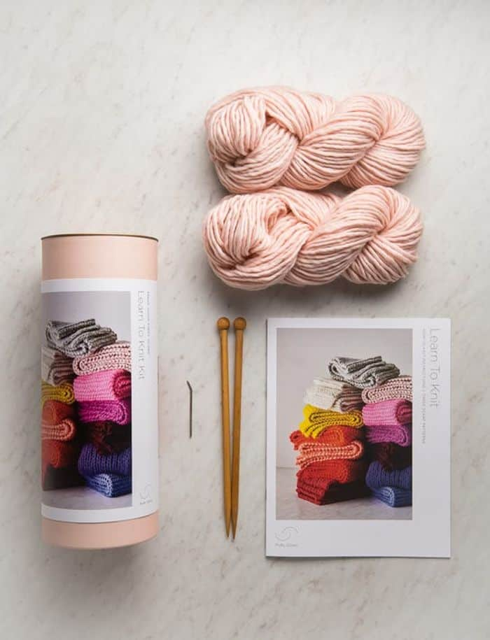 Purl Soho Learn To Knit Scarf Kit. Wooden straight needles, pattern, 2 skeins of yarn in ballerina pink and a tin that it is packaged in.
