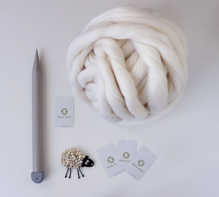 Giant Arm Knitting Kit by Wool Hugs showing a ball of Merino Roving Wool in white. A giant plastic grey knitting needle